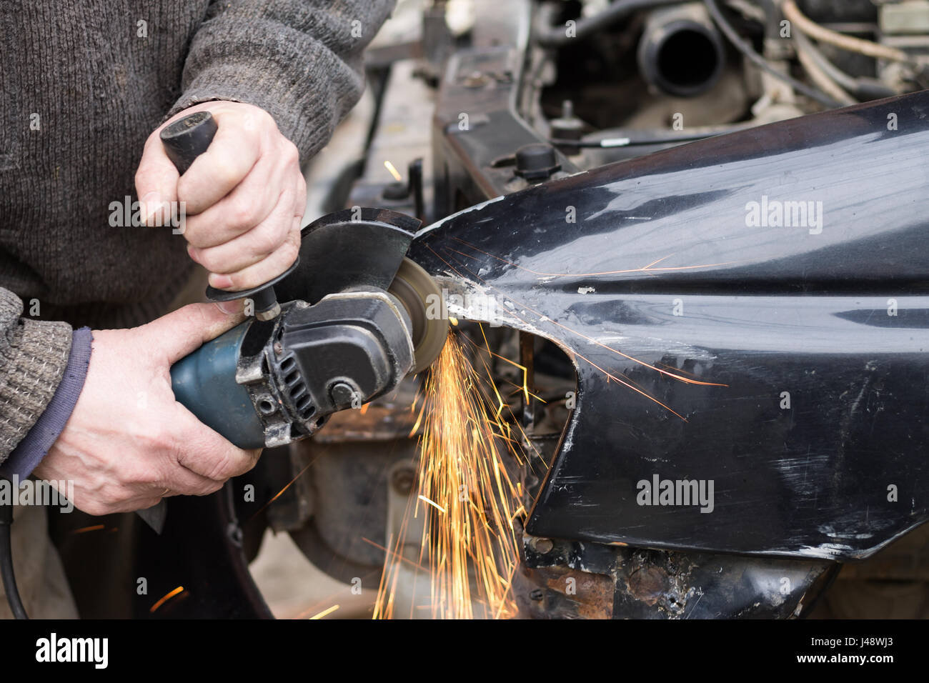 Repair service worker fix damaged car after crash on the road. Working with angle grinder to fix metal body. - Stock Image