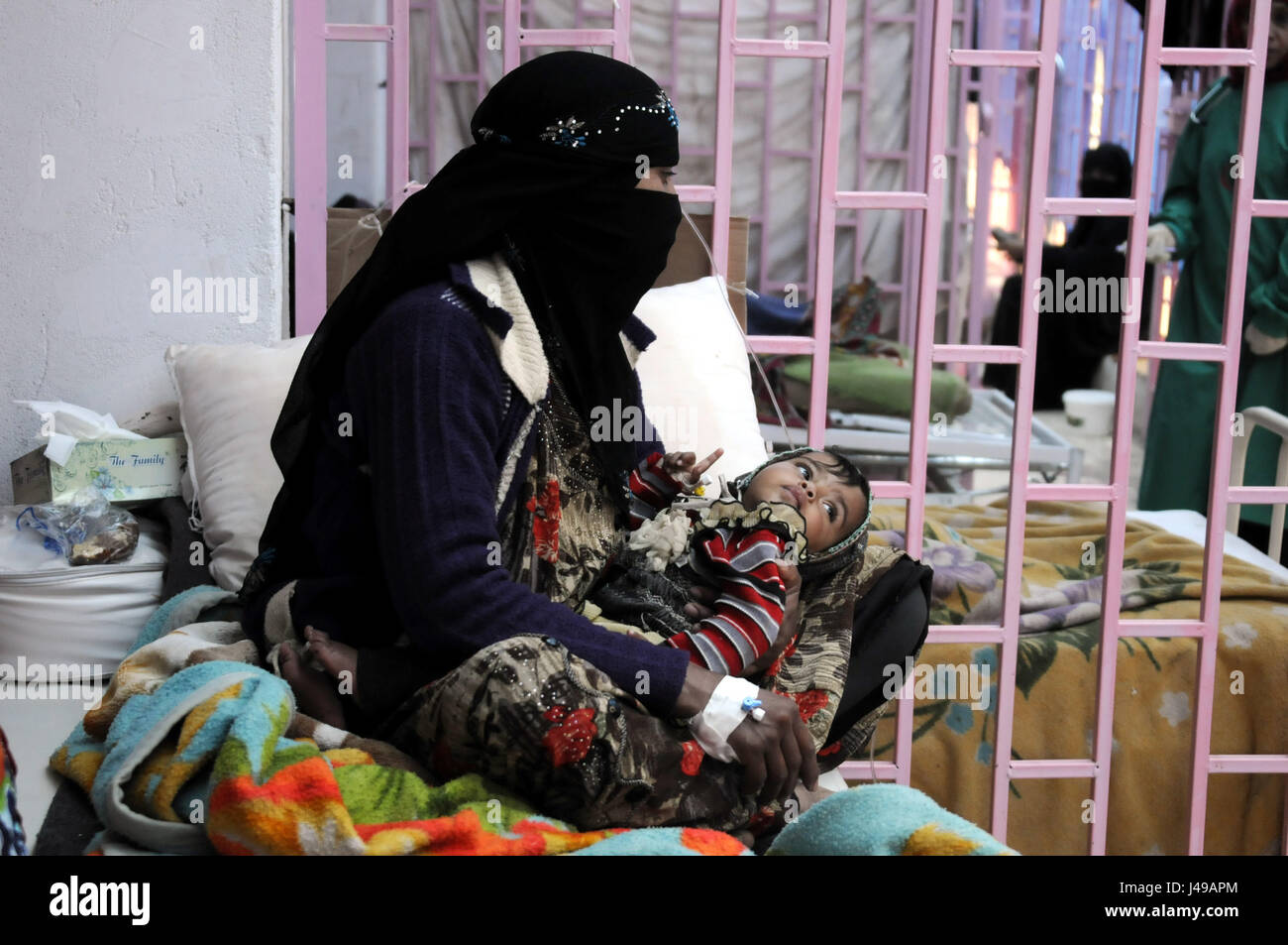 Sanaa, Yemen. 10th May, 2017. A woman holds her baby who is suffering from cholera in a hospital in Sanaa, Yemen, - Stock Image