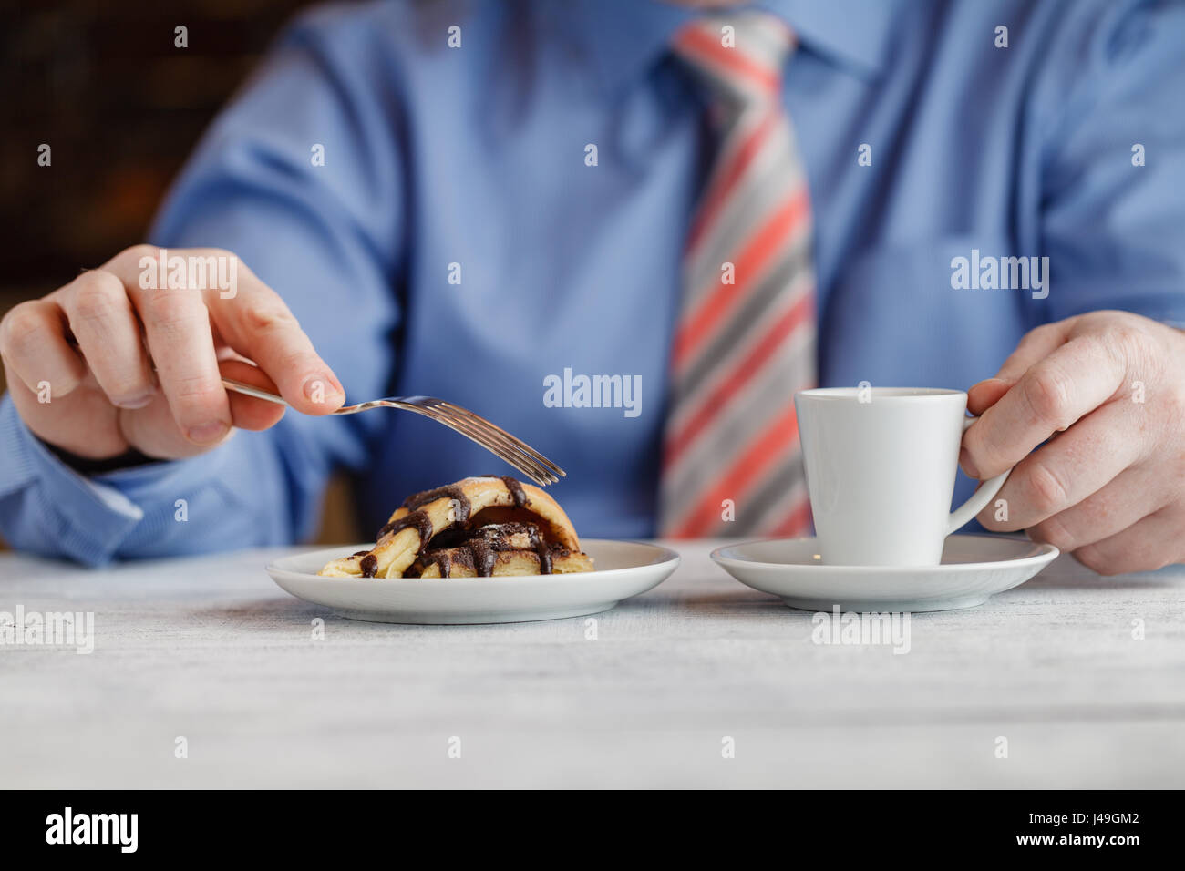 hand cutting homemade caramel custard cake on white plate. On wooden table - Stock Image