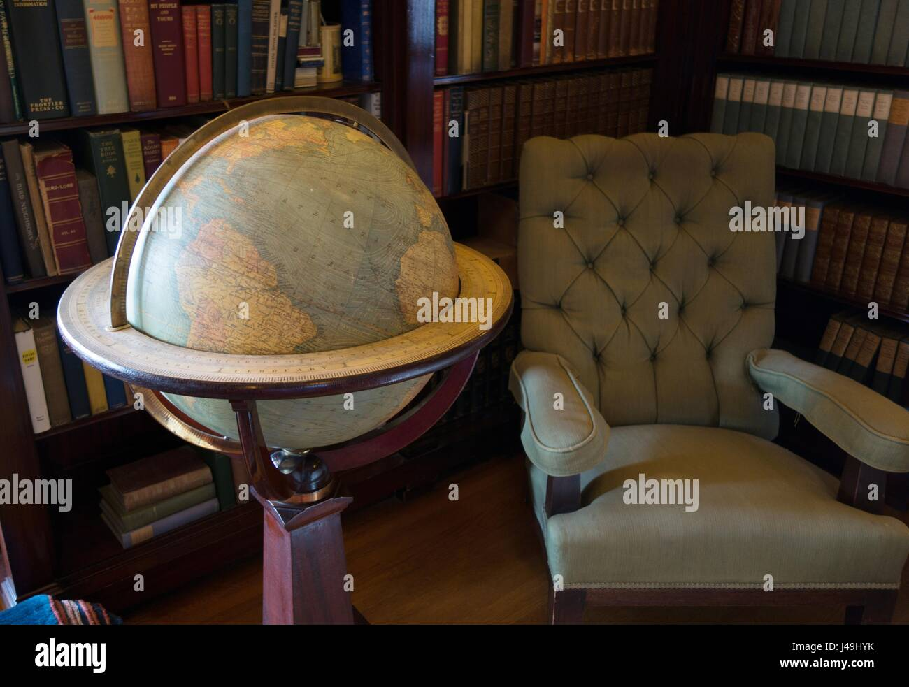 A globe, chair, and books, in a reading room at Glensheen Mansion in Duluth, Minnesota, USA. - Stock Image