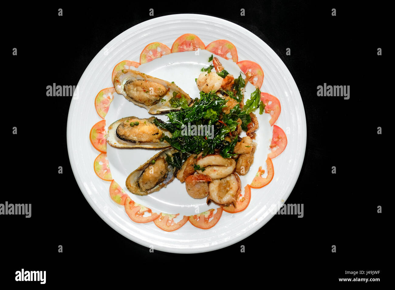 Plate of Asian Style Sesame ginger scallop with hoisin sauce and Shrimp Skewers in black background - Stock Image