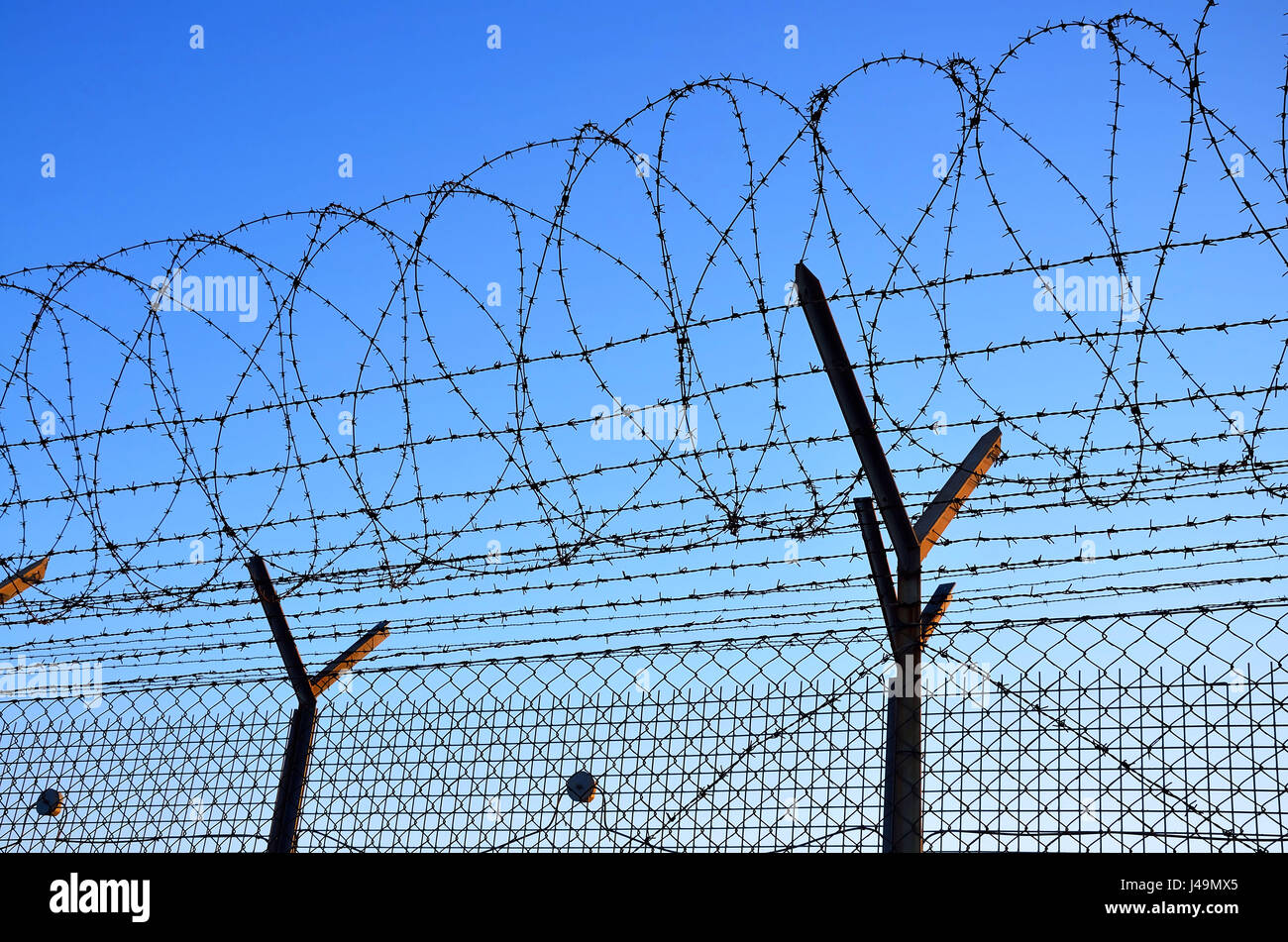 Fence with barbed wire on the blue sky. - Stock Image
