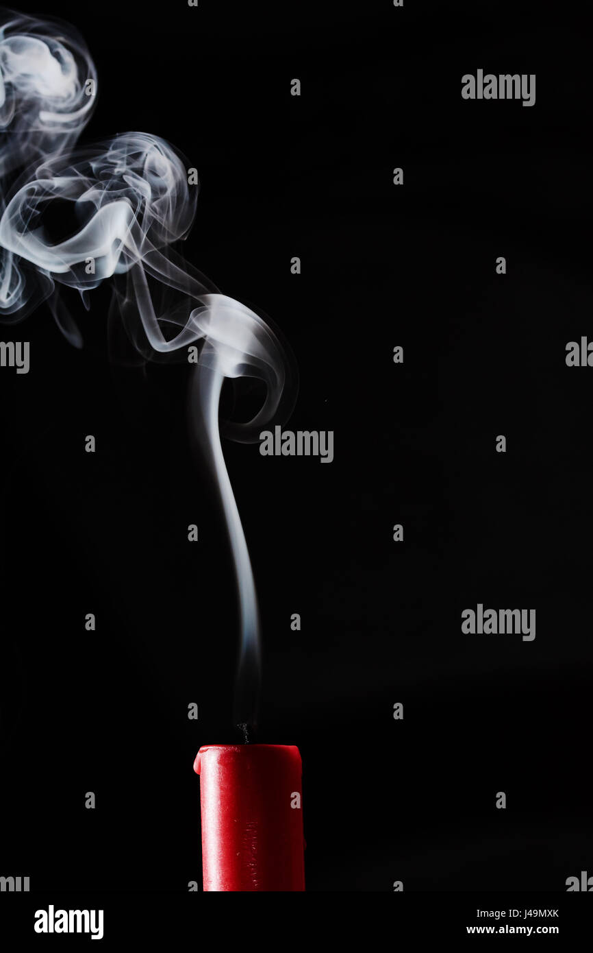 Extinguished candle with smoke trailing off the wick - Stock Image
