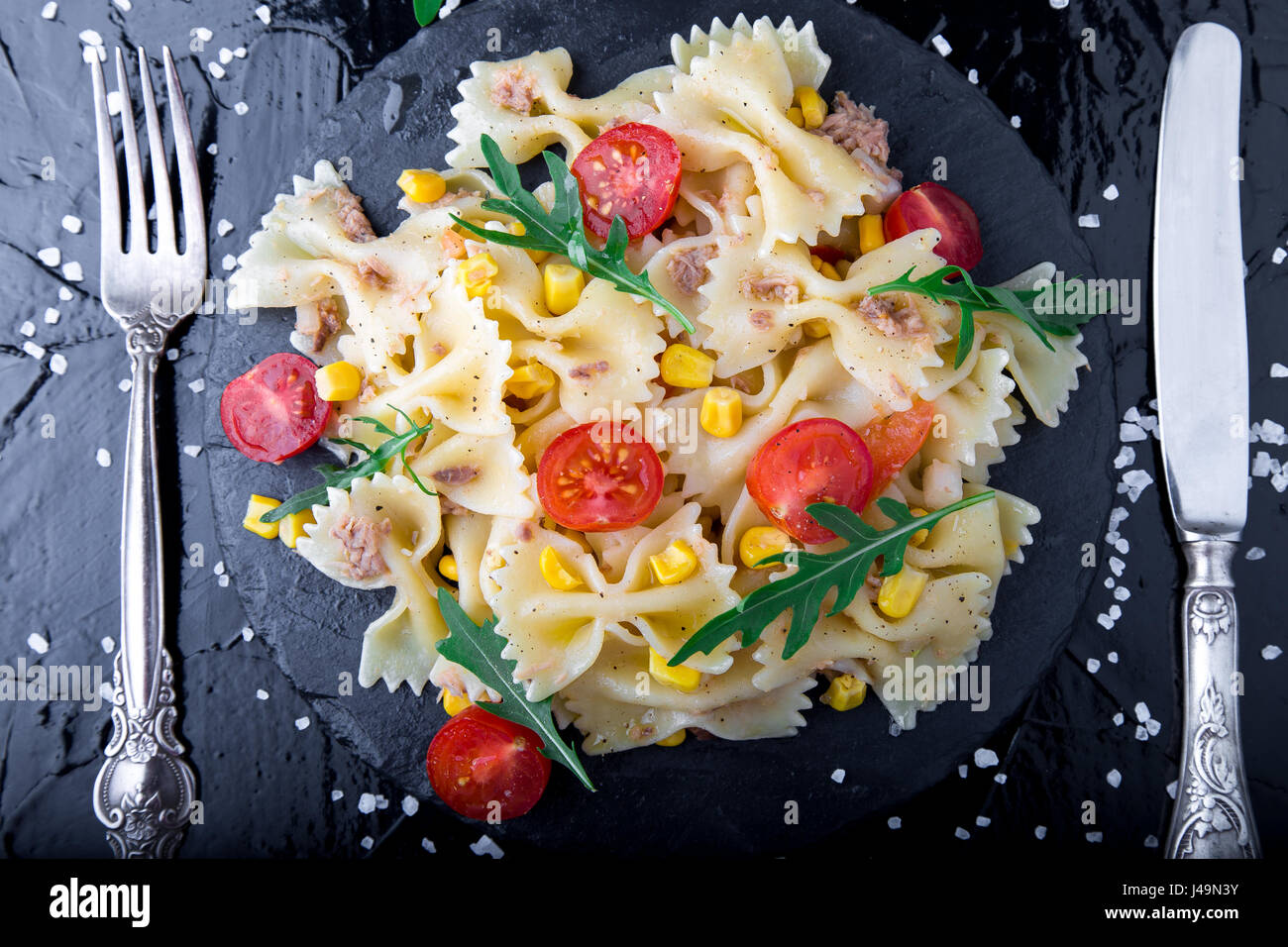 Pasta salad in slate plate with tomatoes cherry, tuna, corn and arugula near knife and spoon. Top view. ingredients. - Stock Image