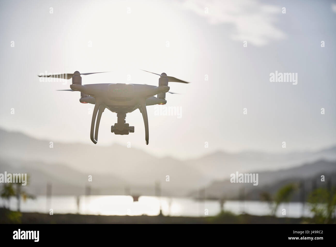Drone flying with the sun and sky behind - Stock Image