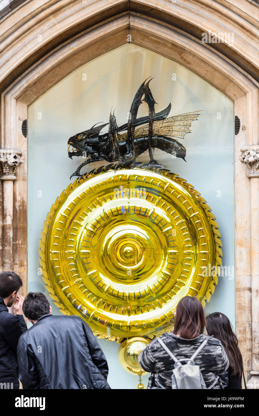 Tourists examine the chronophage (time-eater) and large clock designed by John Taylor outside Corpus Christi college Stock Photo