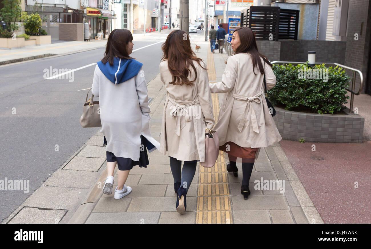 Nagasaki, Japan - March 26th, 2017: Three japanese girls walking on the sidewalk, two of them wearing trench coat. - Stock Image