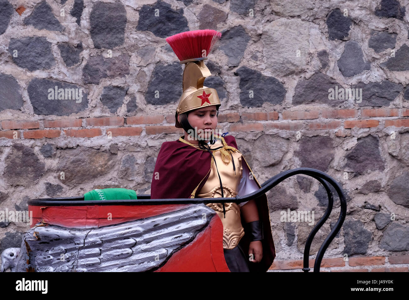 A young boy dresses as a Roman warrior during Semana Santa or Holy week celebration in the city of Antigua Guatemala - Stock Image