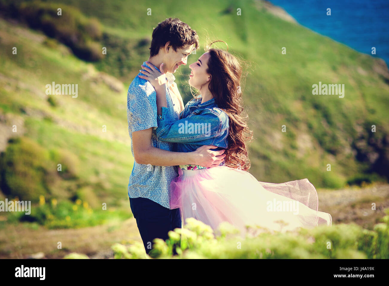 romantic couple embraces in the field. Carefree modern travel concept. - Stock Image
