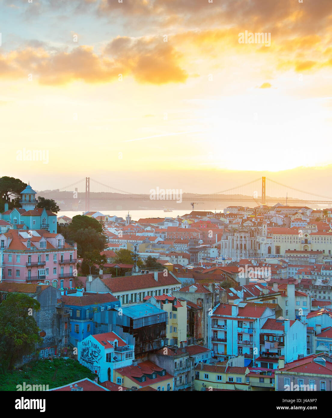 View of Lisbon at sunset with sun in the sky. Portugal - Stock Image