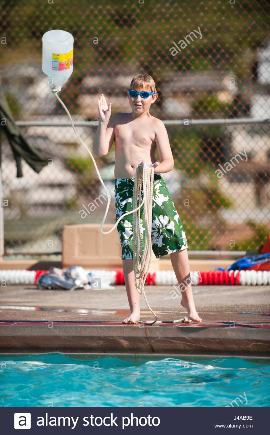 Boy throwing a rescue rope into a swimming pool as he learns the skills needed to earn a Boy Scout merit badge for - Stock Image