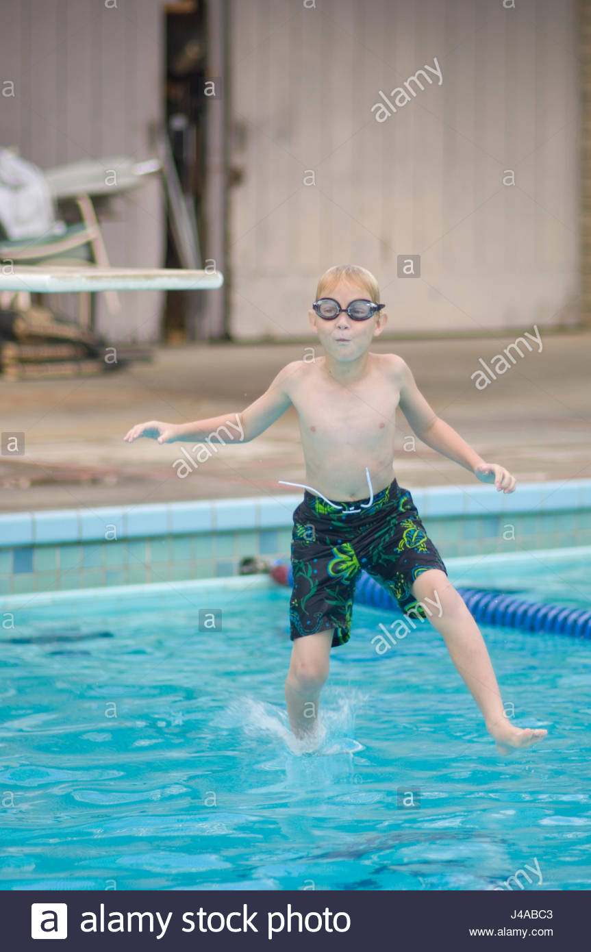 Boy jumping into swimming pool from the end of a diving board Stock ...