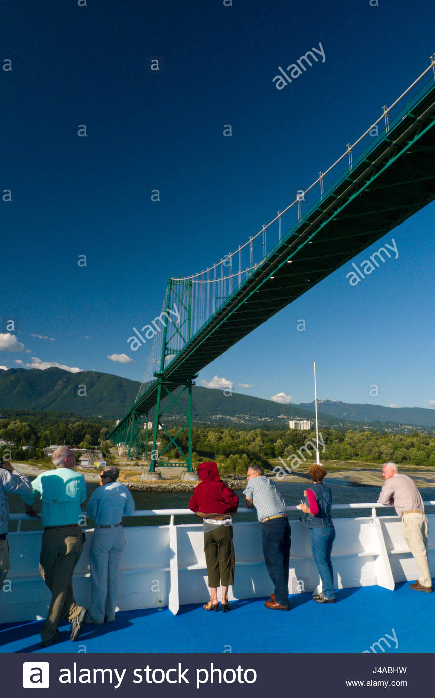 Passengers on the Regency Seven Seas Navigator cruise ship passing under the Lions Gate Bridge, Vancouver, British - Stock Image
