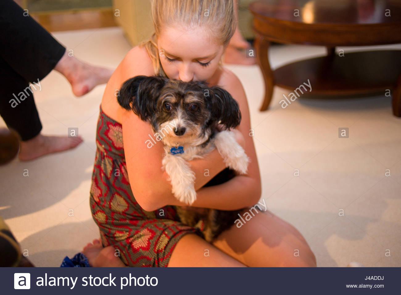 Teenage girl holding small pet dog at home, USA Stock Photo