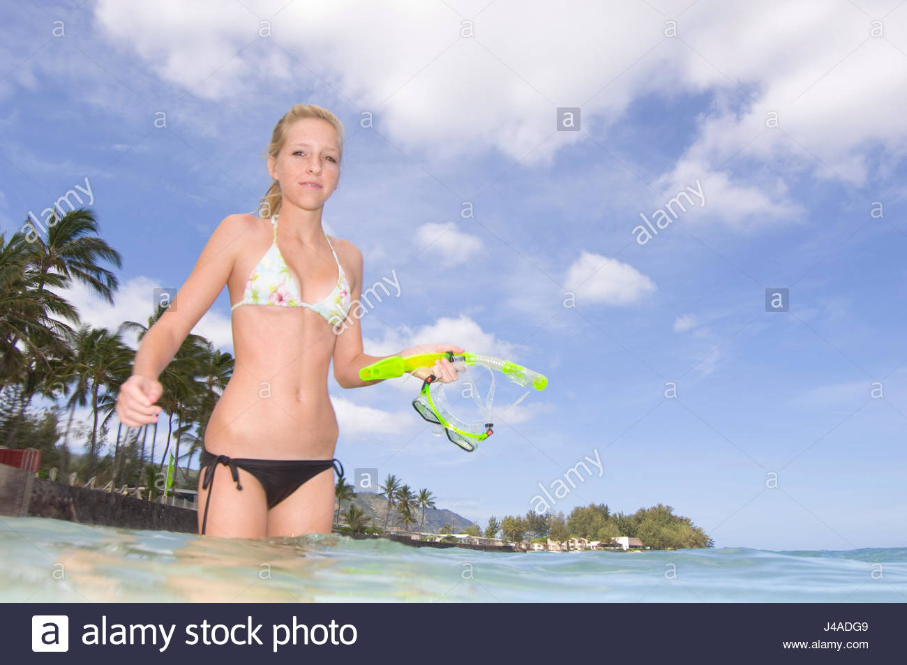 b9ecb6716c Teenage girl with blonde hair wearing a two piece swimsuit standing in the  warm water of the Pacific Ocean off Mokuleia Beach, Oahu, Hawaii, USA