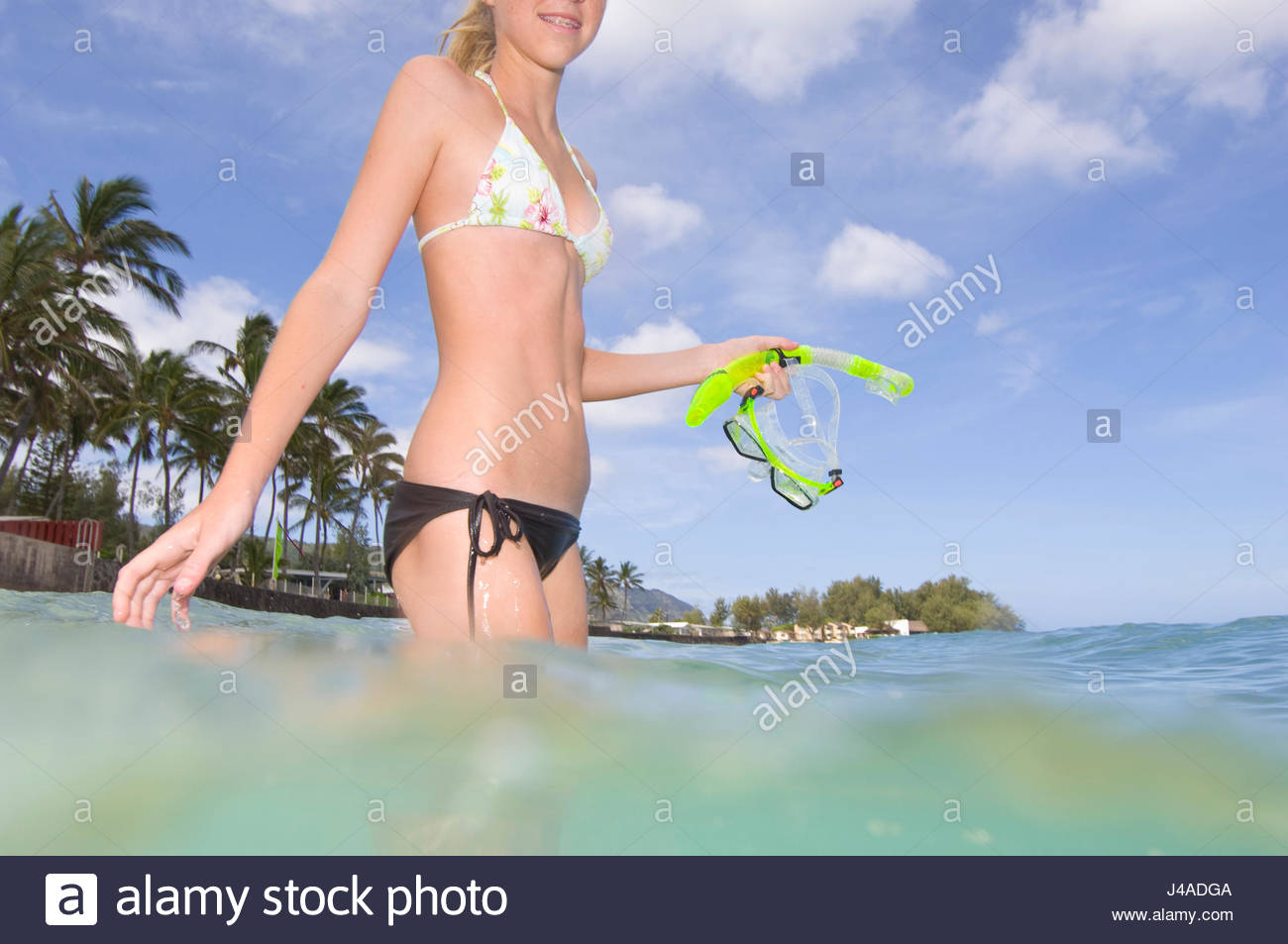 a59a93976444f Teenage girl with blonde hair wearing a two piece swimsuit standing in the  warm water of the Pacific Ocean off Mokuleia Beach