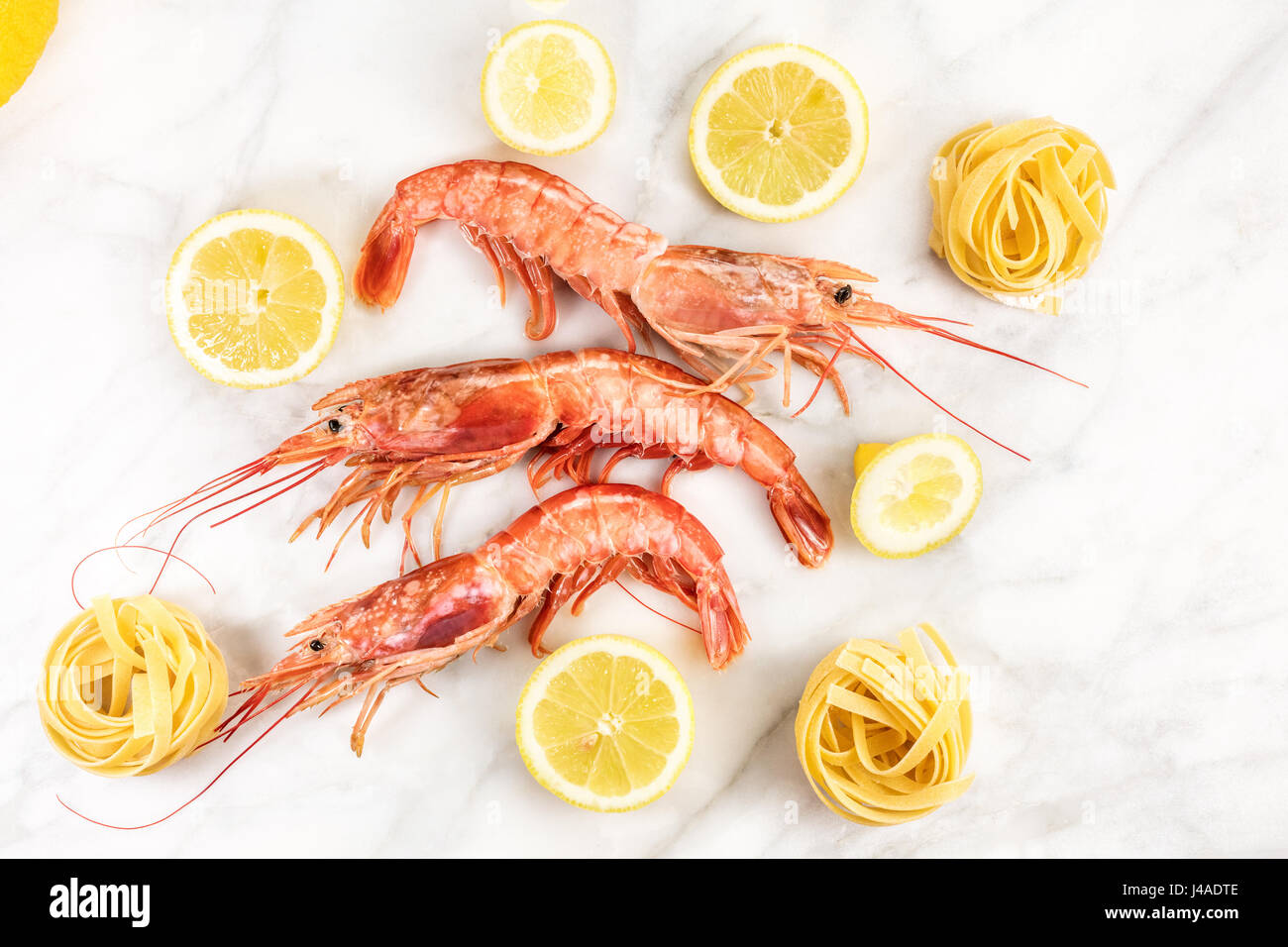 Raw shrimps with lemon and pasta on marble table - Stock Image