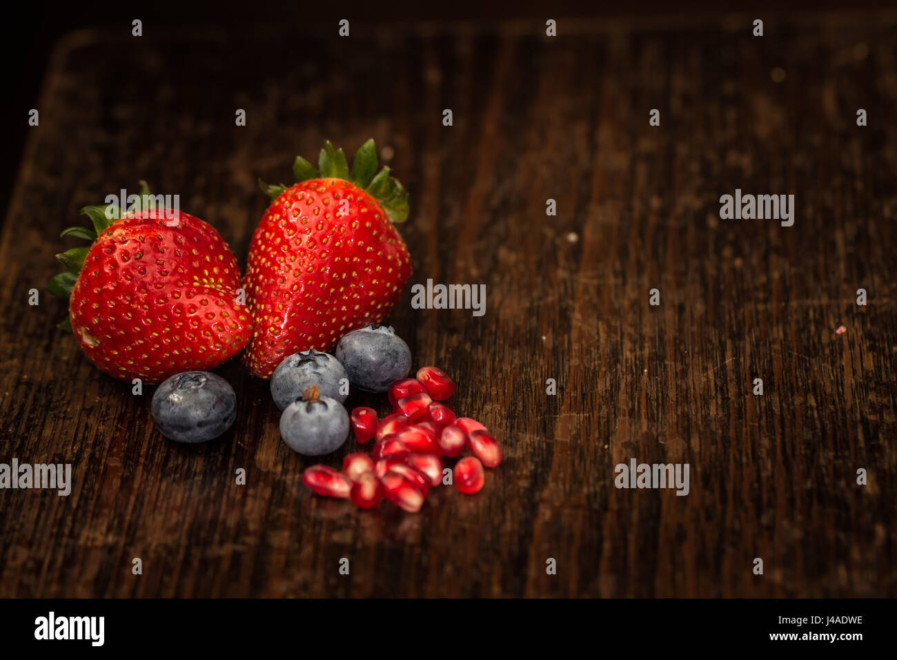 freshly farm picked strawberries blue berries closeup with pomegranate seeds with copy space Stock Photo