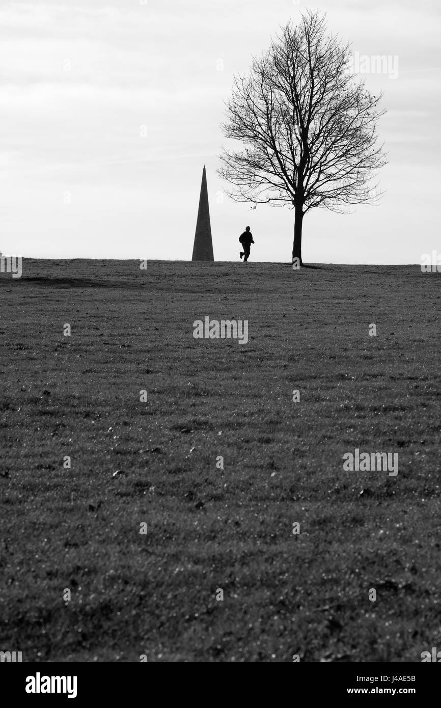 Jogger silhouetted against the spire of Holy Trinity church, Brockwell Park, London, UK - Stock Image