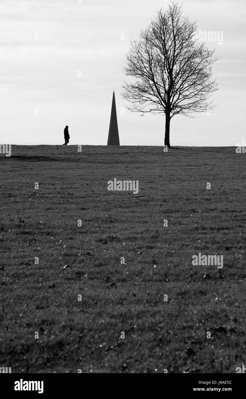 Walker silhouetted against the spire of Holy Trinity church, Brockwell Park, London, UK - Stock Image