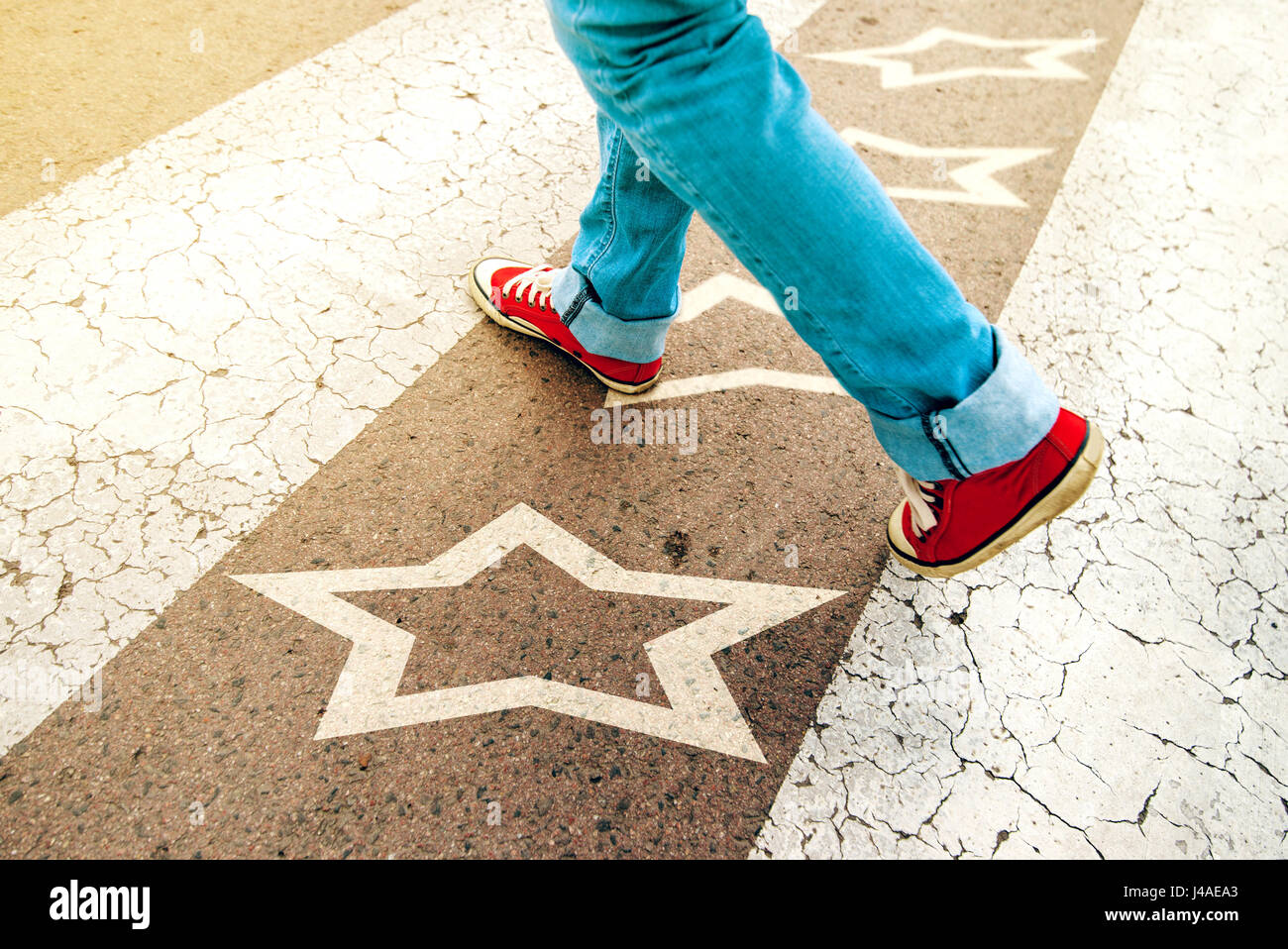 Sneakers on the road with star shape imprint - talent, vip, prize and award concept - Stock Image