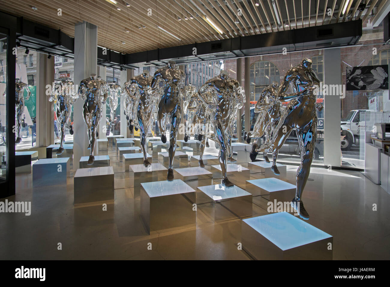 Chrome colored sculptures of headless runners at the Nike Store on Broadway & Spring Street in the Soho section - Stock Image