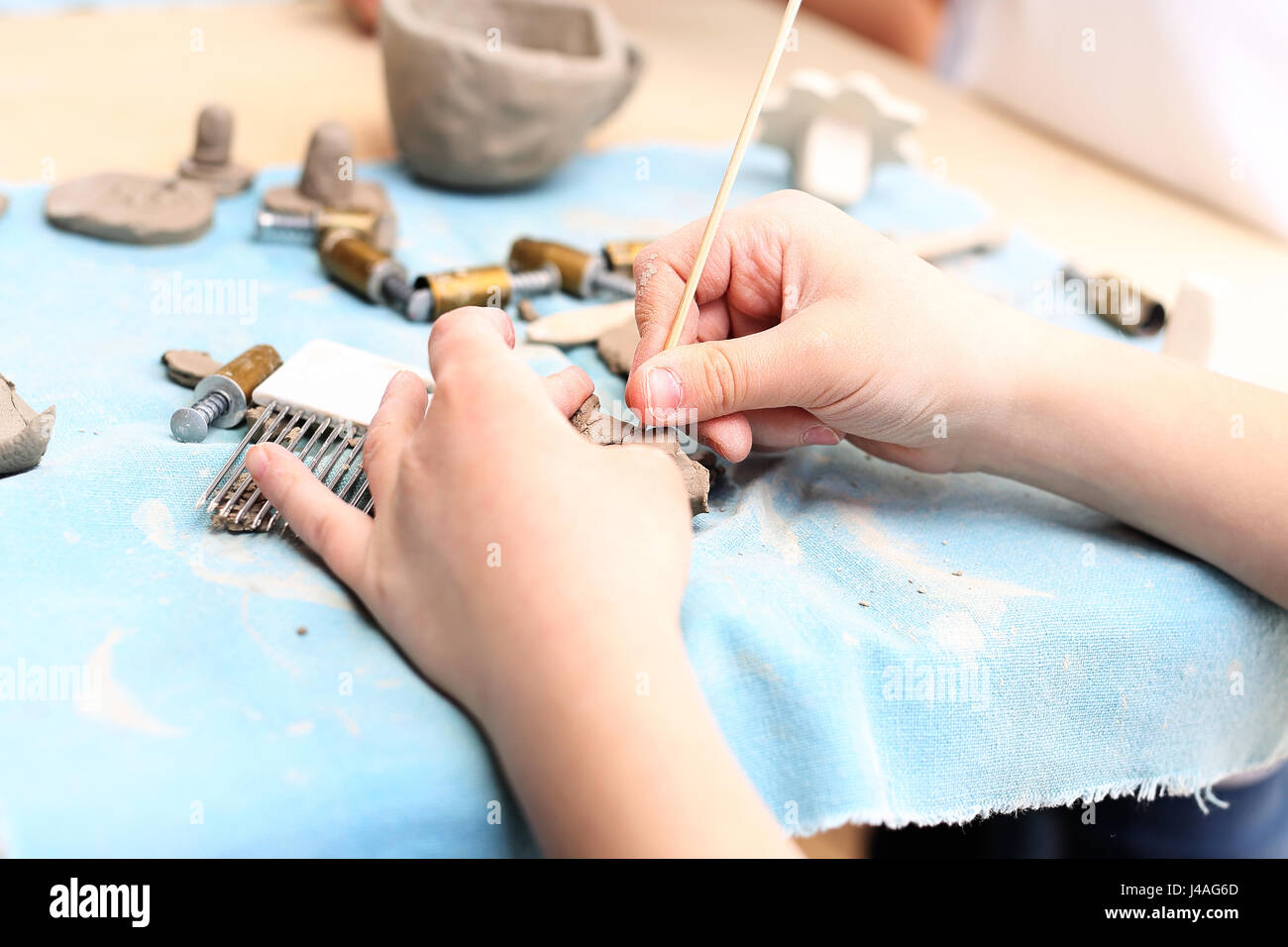 Ceramic course for children. The boy is clawing out of clay at a plastic workshop. Extracurricular activities, ceramics. - Stock Image