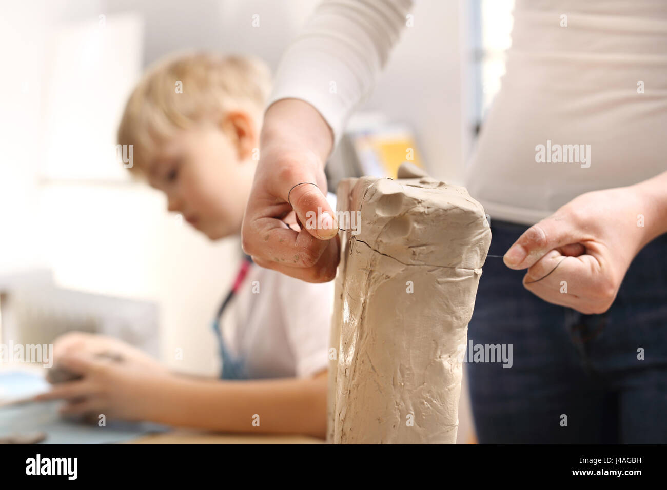 Extracurricular activities, ceramics. Clay for ceramics. Natural clay for ceramics Clipping the clay block with - Stock Image