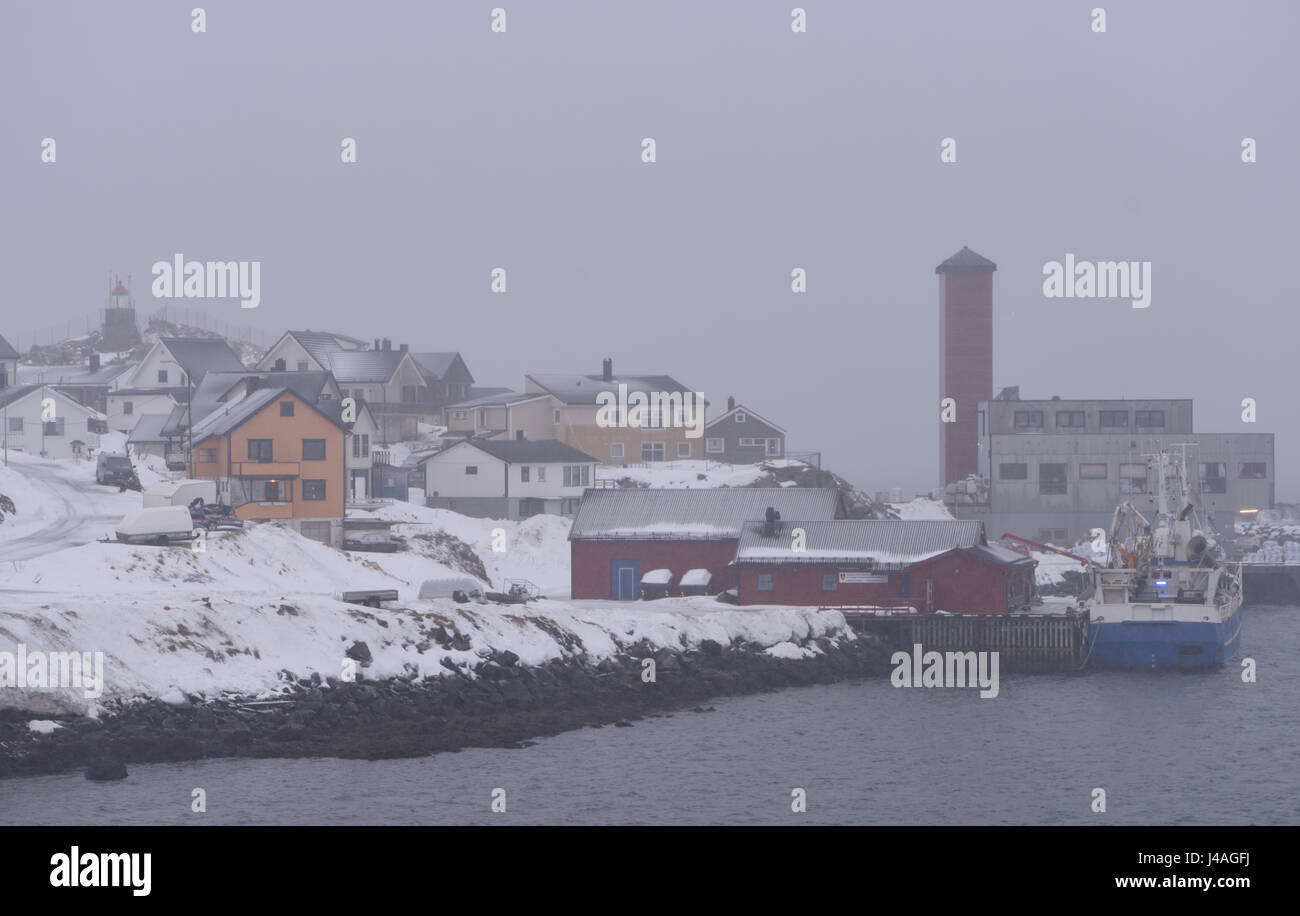 The harbour at Honningsvag, the northernmost city in Norway, on a foggy winter morning. On the skyline are the lighthouse - Stock Image