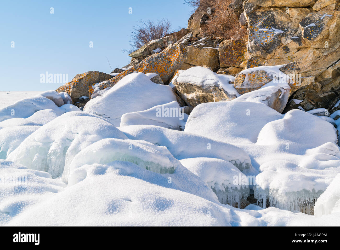 Frozen water and rocks covered with snow at rocky island in Lake Baikal Russia during winter - Stock Image