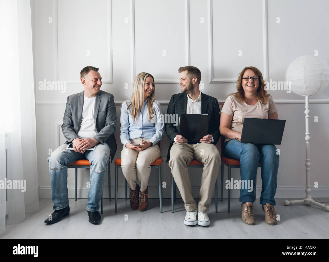 Group of young creative people sitting on chairs in waiting room - Stock Image