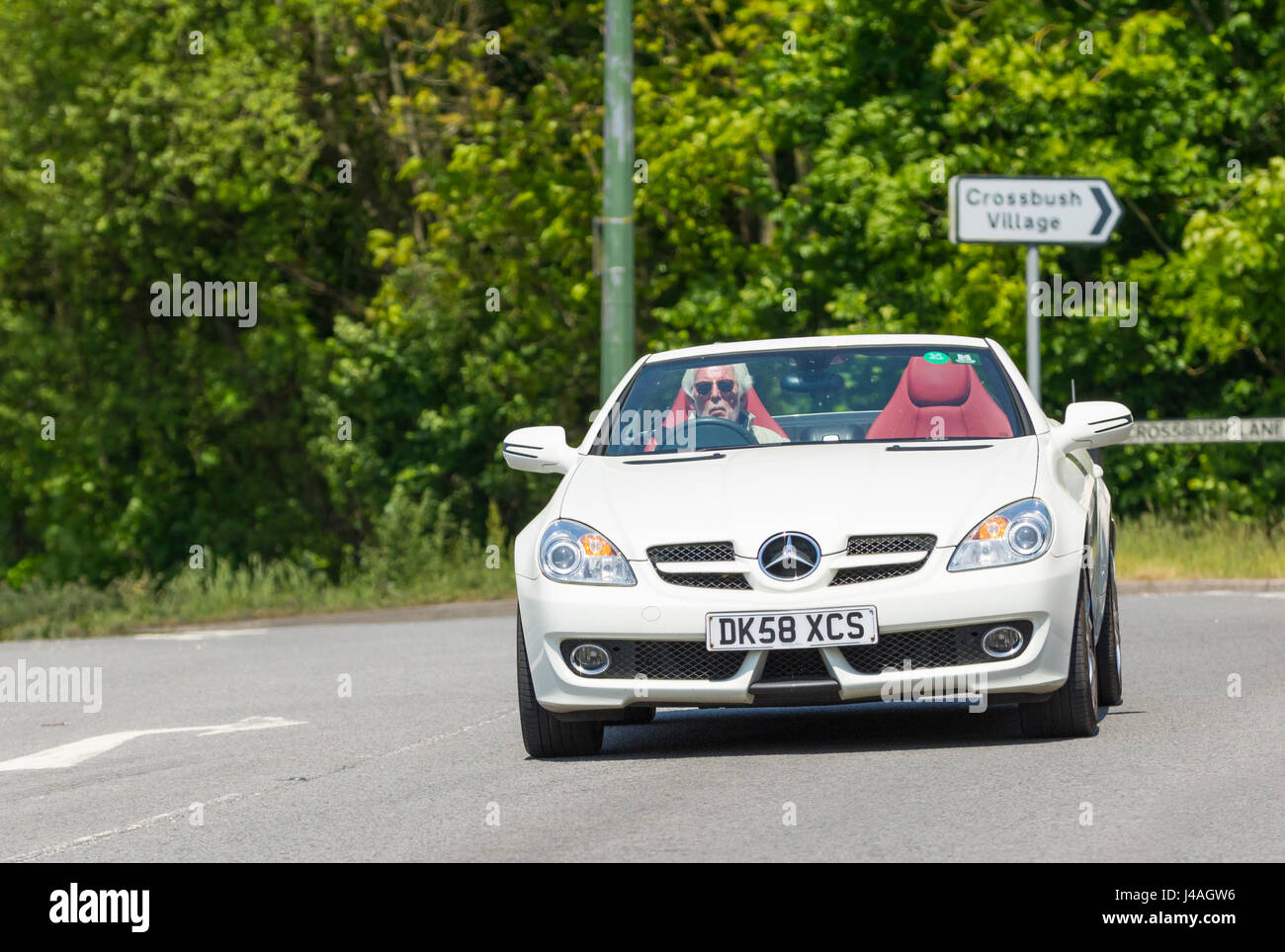 Convertible car. Man driving a luxury car in hot weather with the top down. - Stock Image
