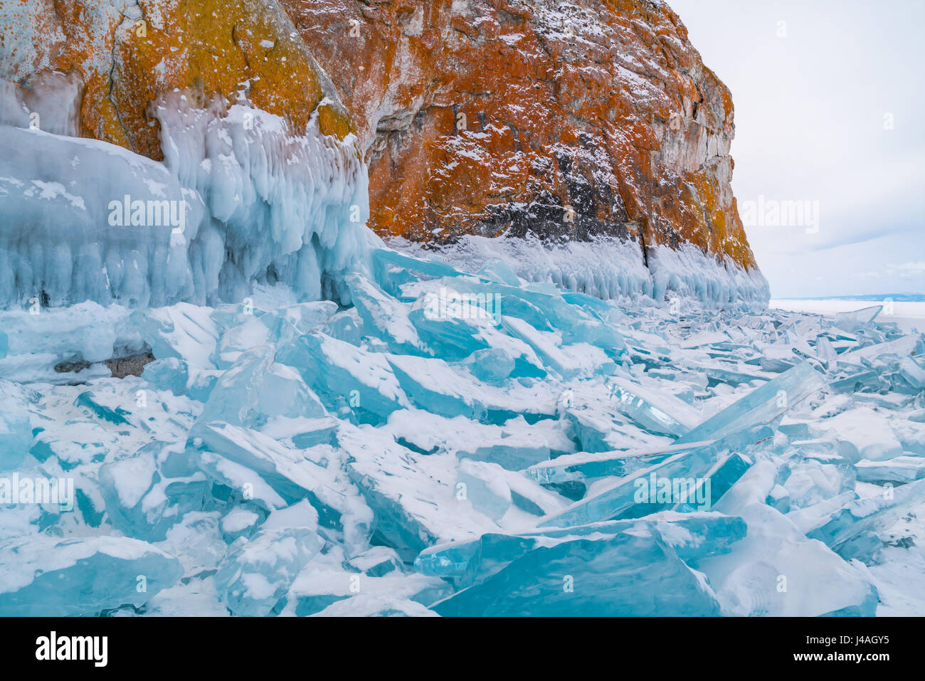 Blue frozen water covered with snow and icicles at rocky island in Lake Baikal, Russia - Stock Image