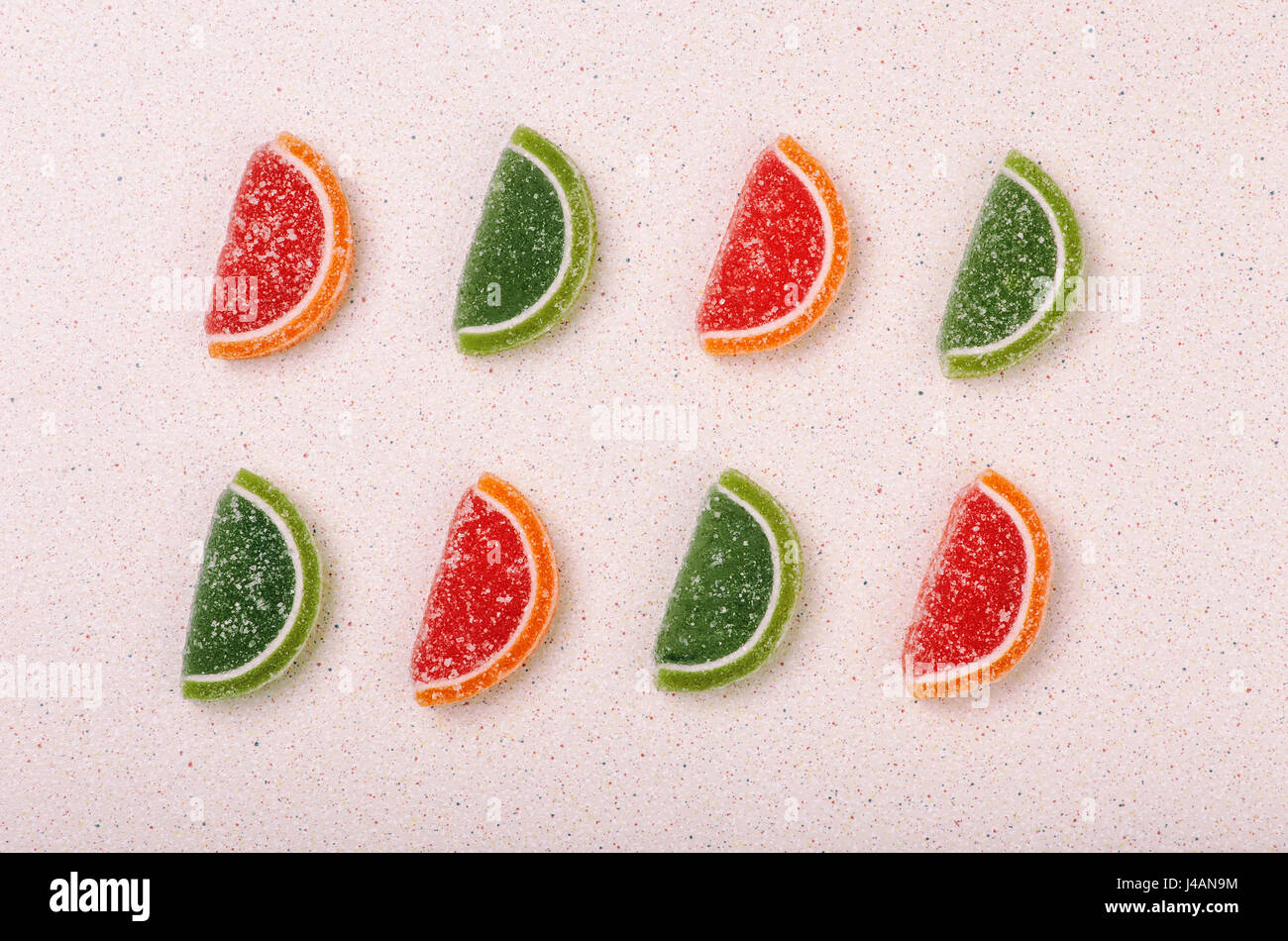 Still life of marmalade slices of citrus fruit lined with a color pattern. - Stock Image