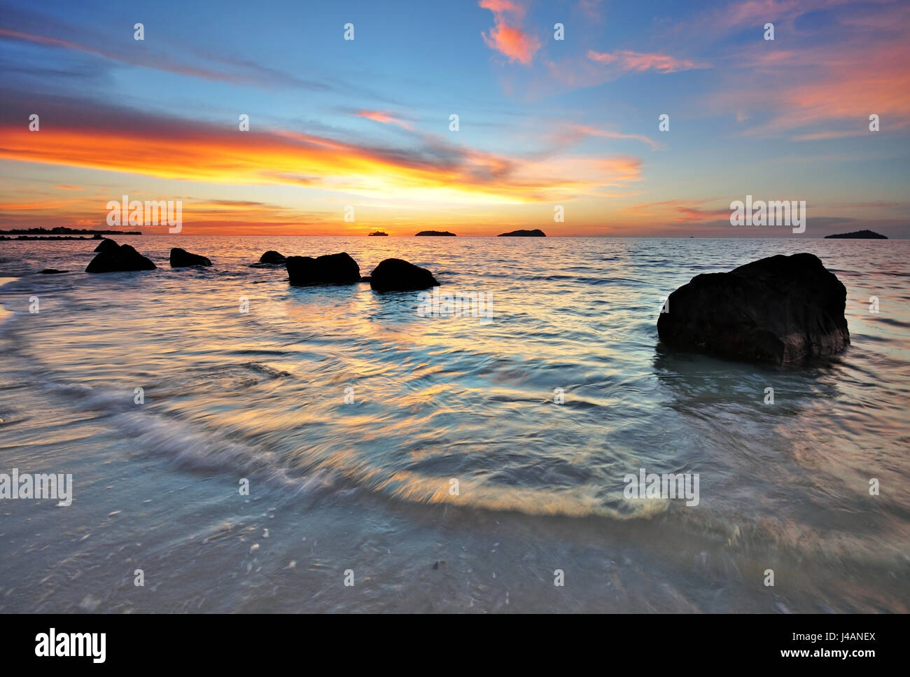 Beautiful sunset in a rocky beach in Kota Kinabalu, Sabah Borneo, Malaysia. - Stock Image