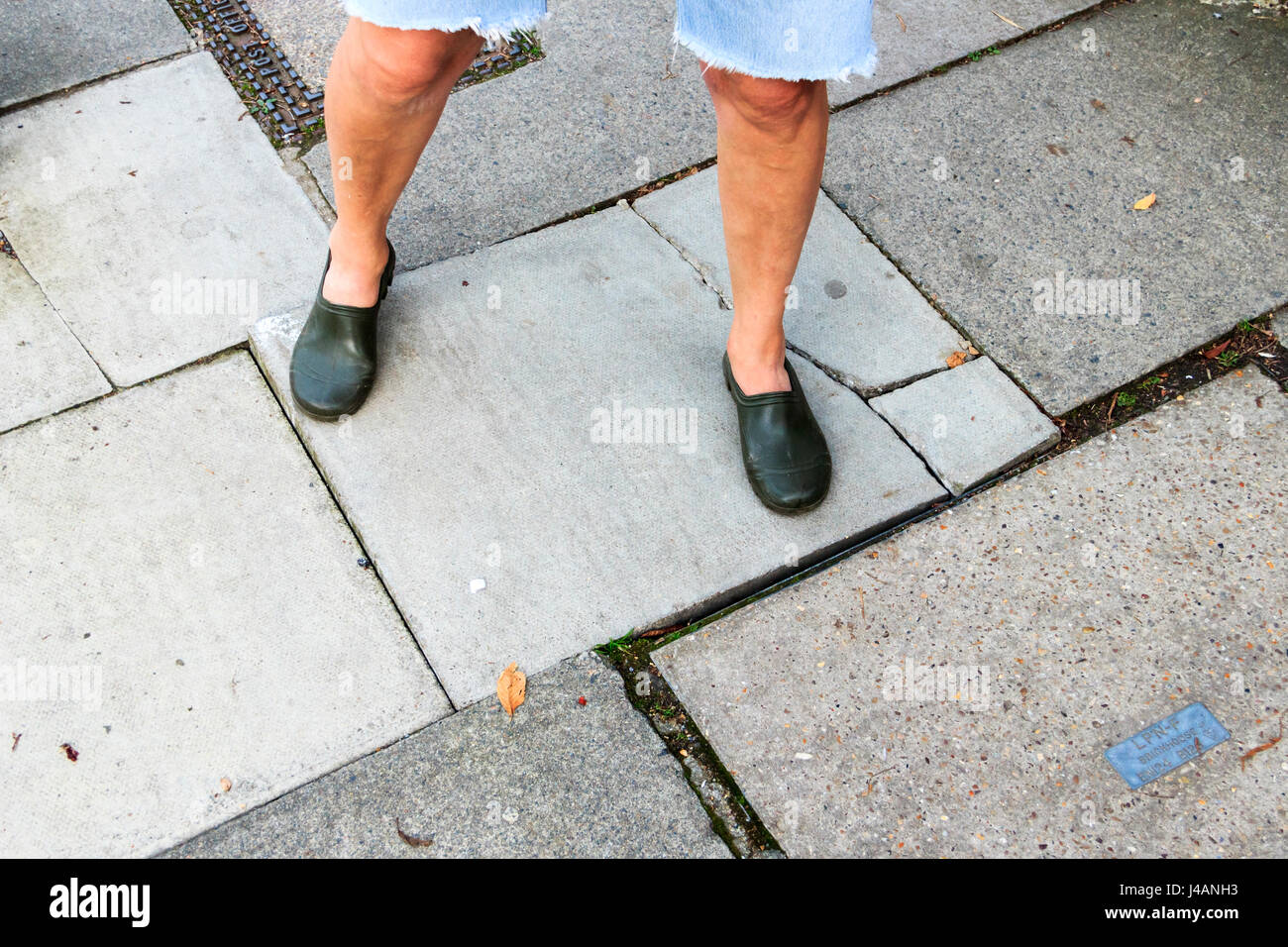 A woman with bare legs standing on a cracked paving stone, Islington, London, UK - Stock Image