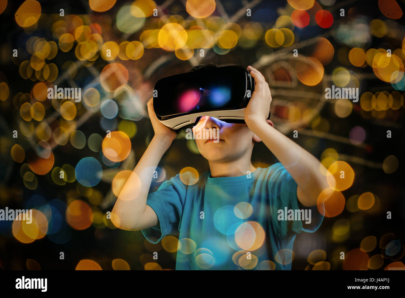Child playing with a virtual reality headset. Young boy wearing and learning with a VR goggles. - Stock Image