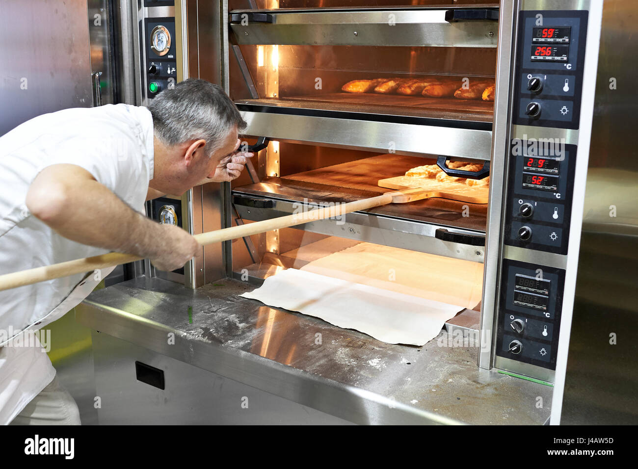 Baker bakes bread in the oven - Stock Image