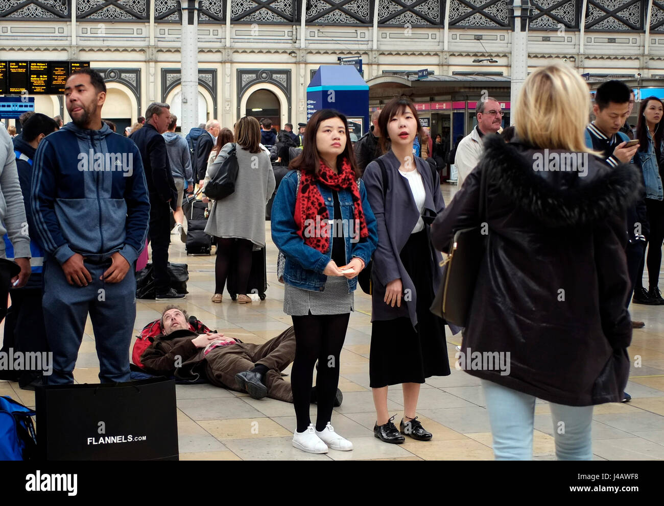 A man lays on the ground in the concourse of London Paddington station, in London, Britain May 1, 2017. © John - Stock Image