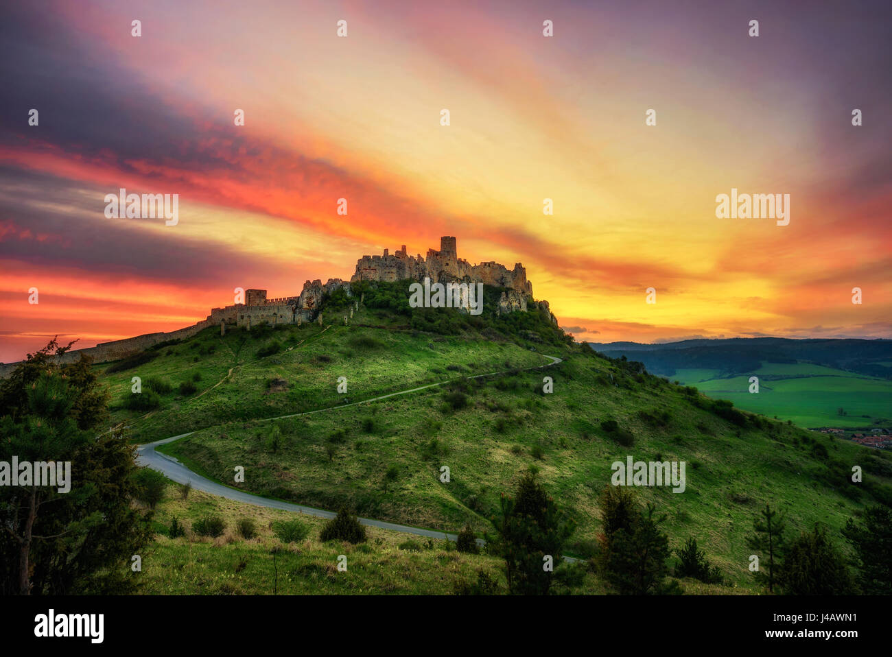 Dramatic sunset over the ruins of Spis Castle in Slovakia.  Spis Castle is a national monument and one of the biggest - Stock Image