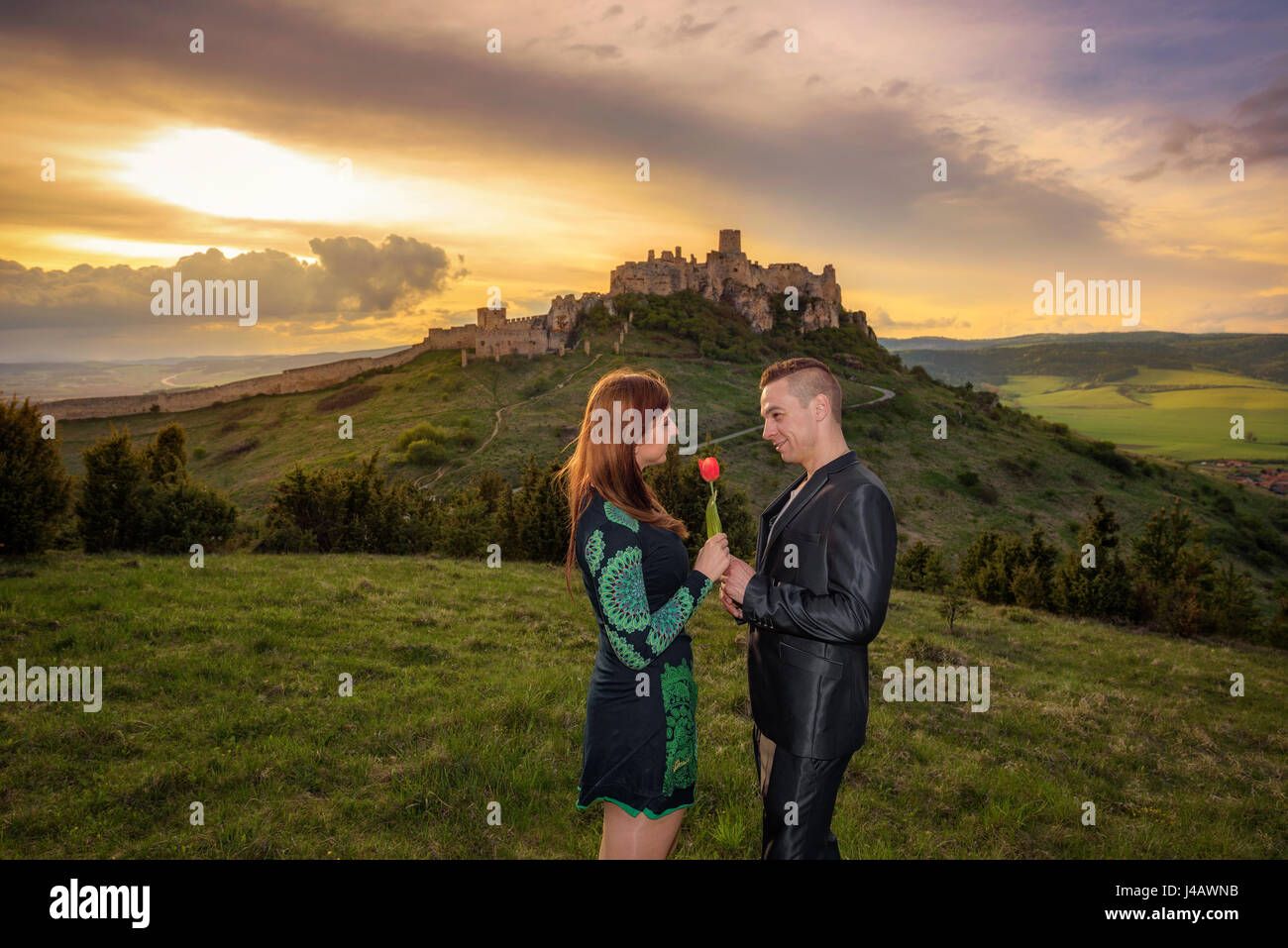 Young couple in love at sunset near a ruined castle. The man is giving a red tulip to his girlfriend. - Stock Image