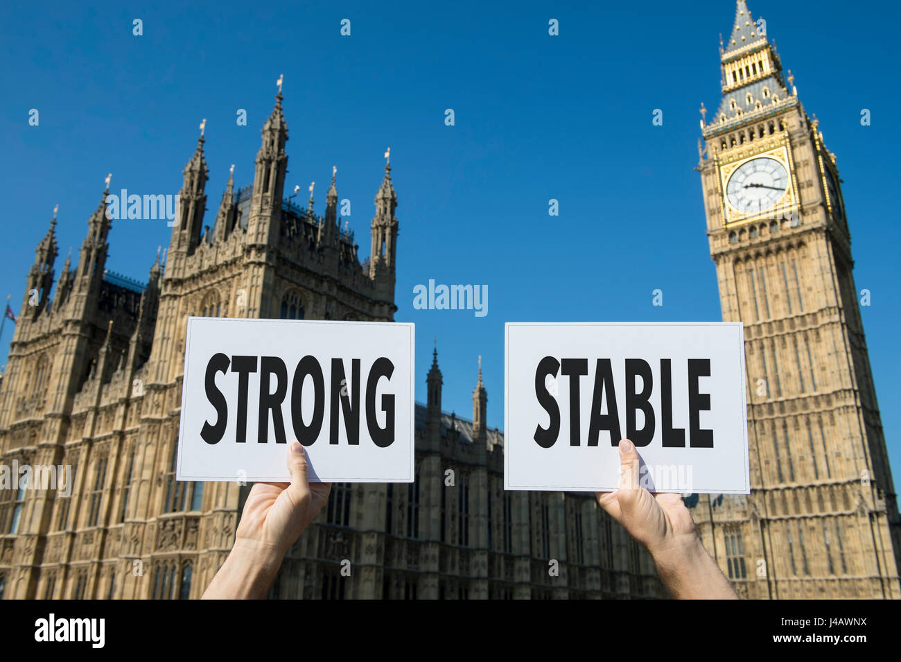 Hands holding protest signs with the message 'Strong, Stable' referring to the United Kingdom and its relationship - Stock Image