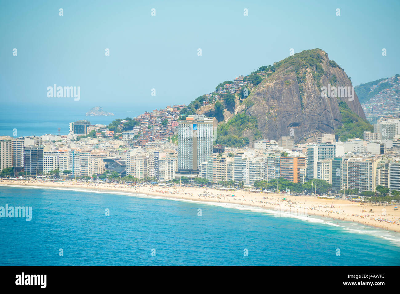 Bright scenic view of the golden crescent of Copacabana Beach with the city skyline of Rio de Janeiro, Brazil - Stock Image