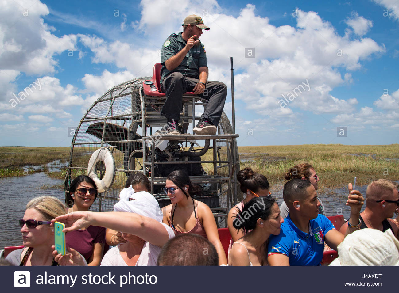 Tourists and guide in airboat exploring the Everglades.  The Everglades (or Pa-hay-okee) is a natural region of - Stock Image