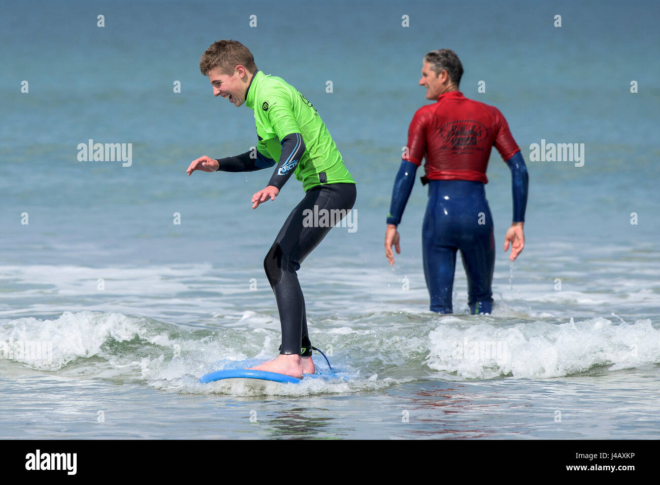 A novice learning to surf on Fistral Beach in Newquay Cornwall Escape Surf school Surfing Surfers Learners Learning - Stock Image
