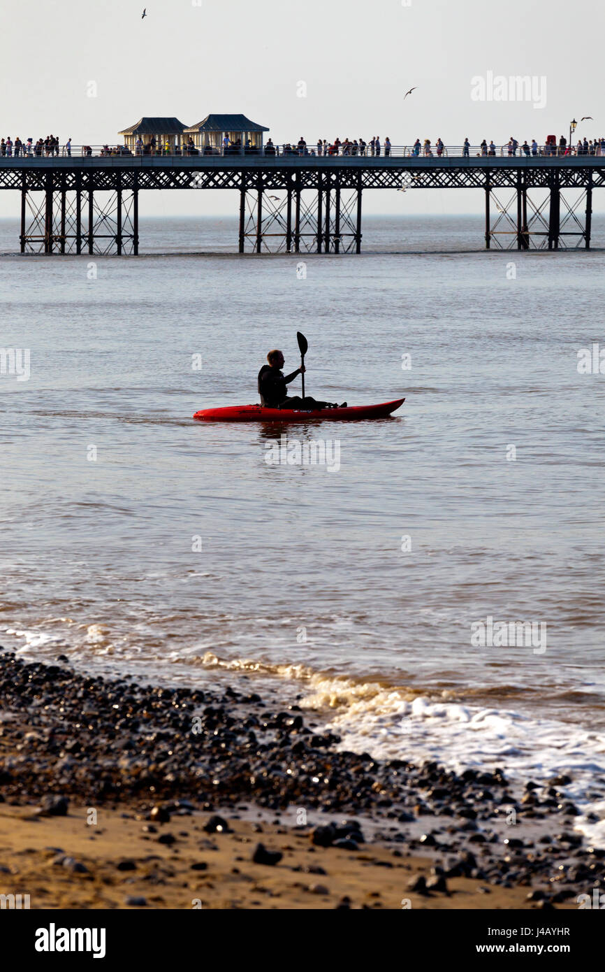 Cromer Pier on the North Norfolk coast England UK built in 1902 with man in kayak in foreground - Stock Image