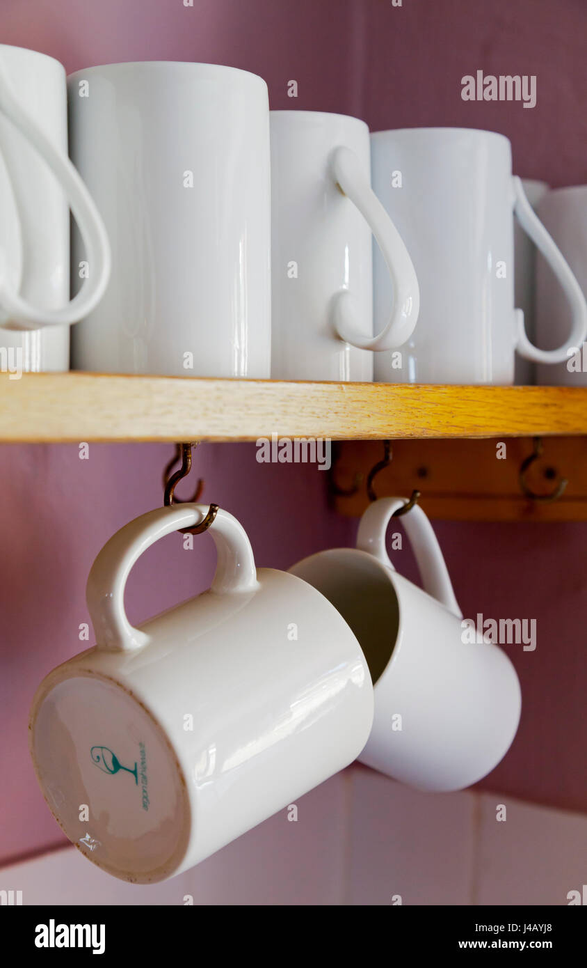 Close up view of white mugs on a wooden shelf - Stock Image