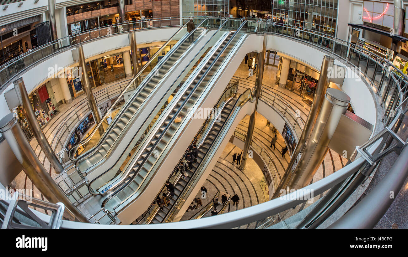 Fish eye view of escalators with people rushing through in a shopping centre in Canary Warf, London - Stock Image