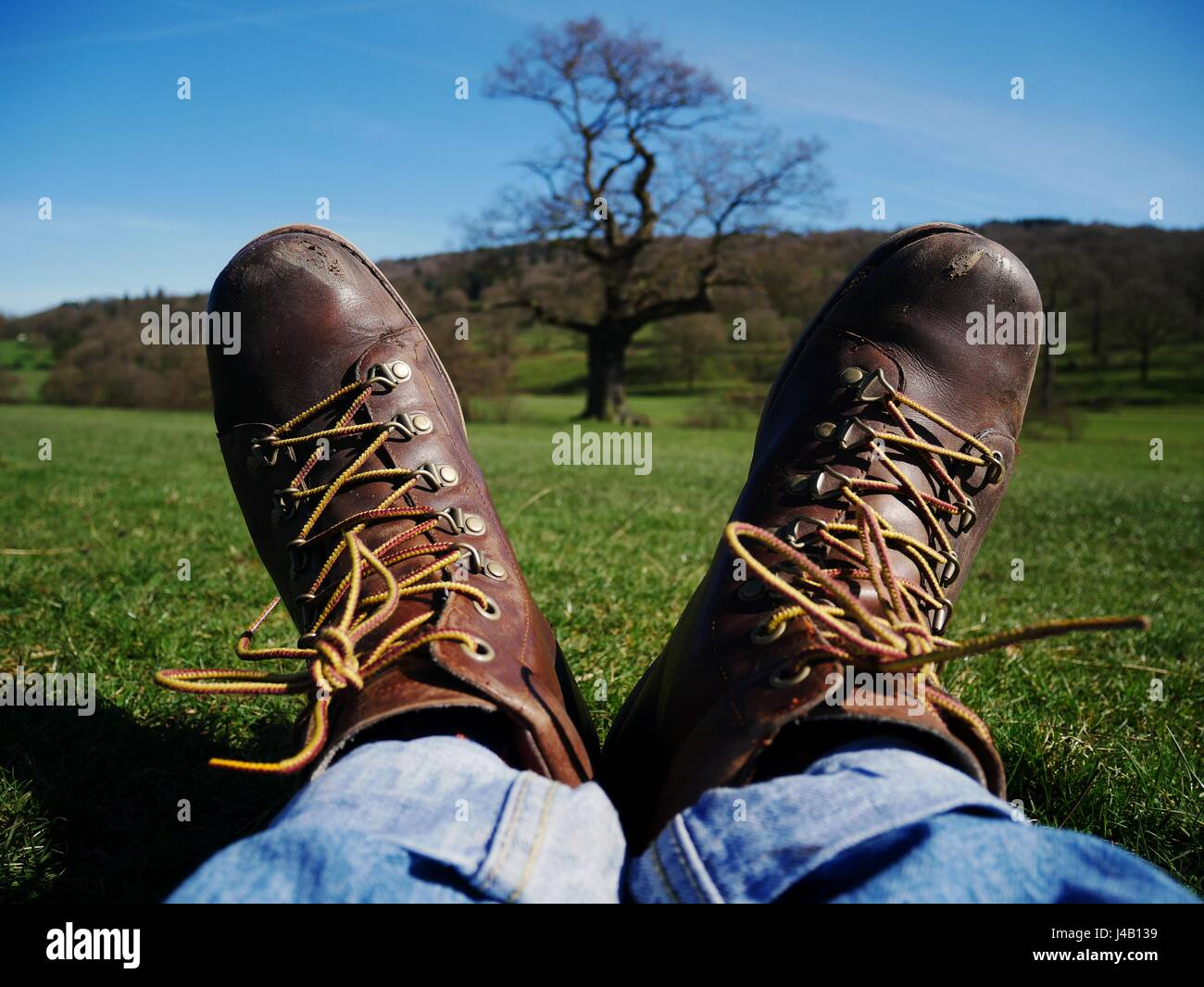 Hiker taking a rest on grass with scuffed brown leather hiking boots, Derbyshire, UK - Stock Image