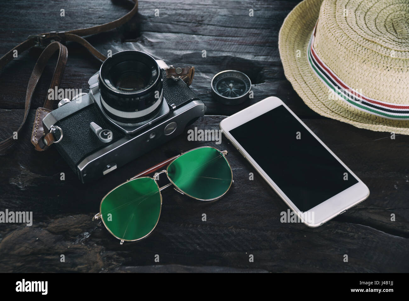 travel accessories on desk such as camera eyeglasses compass hat smart phone technology,travel equipment for blogger - Stock Image